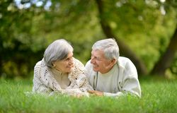 Happy elderly couple. Lying in autumn park Royalty Free Stock Photography