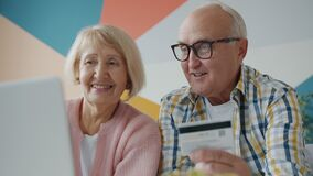 Happy elderly couple making payment online with credit card enjoying shopping