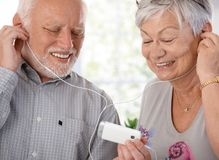 Happy elderly couple with mp3 player. Happy elderly couple using mp3 player, listening to music, smiling Stock Image