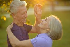 Happy elderly couple. At nature on sunset background Stock Photo