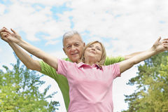 Happy elderly couple outdoors. Happy elderly couple with raised arms outdoors Stock Image