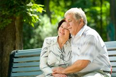 Happy elderly couple outdoors. Happy elderly couple listening music in headset together, outdoors Royalty Free Stock Photography