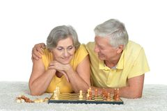 Happy elderly couple playing chess. At home royalty free stock images