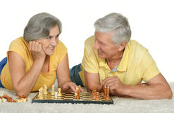 Happy elderly couple. Playing chess at home Royalty Free Stock Image