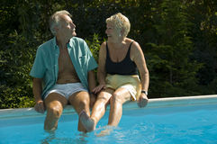 Happy elderly couple on pool. Happy elderly couple having fun while sitting on the poolside and teasing each other Royalty Free Stock Photos