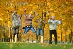 Happy elderly couple. Portrait of happy elderly couple and children jumping in autumn park Stock Photography