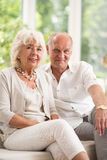 Happy elderly couple. Portrait of happy elderly couple sitting on couch Royalty Free Stock Image