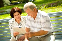 Happy elderly couple reading Stock Photography