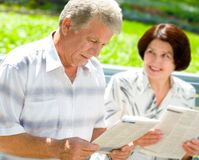 Happy elderly couple reading. Together outdoors. Focus on man Stock Image