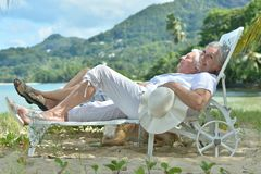 Portrait of happy elderly couple resting in chaise lounges at tropical beach royalty free stock images