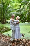 Elderly couple rest at tropical beach. Happy elderly couple resting at tropical beach Royalty Free Stock Photography