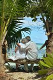 Couple resting  at tropical beach. Happy elderly couple resting  at tropical beach pointing with finger Royalty Free Stock Image