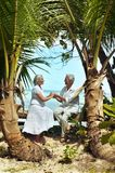 Couple resting  at tropical beach. Happy elderly couple resting  at tropical beach pointing with finger Royalty Free Stock Photography