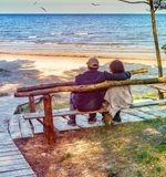 Happy elderly couple resting on the wooden bench Stock Photos