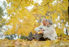 Happy elderly couple. Sitting in autumn nature royalty free stock image
