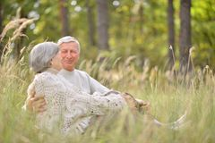 Happy elderly couple. Sitting in autumn park Royalty Free Stock Photo
