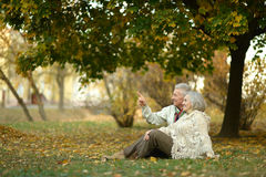 Happy elderly couple. Sitting in autumn park,man shows something by his hand Stock Images
