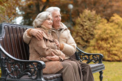 Happy elderly couple sitting on a bench in autumn park. Portrait of a happy elderly couple sitting on a bench in autumn park Stock Photography