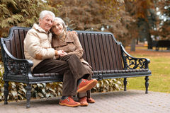 Happy elderly couple sitting on a bench in autumn park. Portrait of a happy elderly couple sitting on a bench in autumn park Royalty Free Stock Photo