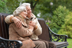 Happy elderly couple sitting on a bench in autumn park. Portrait of a happy elderly couple sitting on a bench in autumn park Stock Image