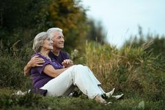 Happy elderly couple. Sitting on grass in park Royalty Free Stock Image