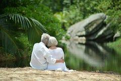 Happy elderly couple sitting. On tropical  beach Royalty Free Stock Photos