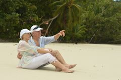 Happy elderly couple sitting. On tropical  beach,man pointing with finger Stock Images