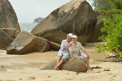 Happy elderly couple sitting on a large rock on the beach. Happy beautiful elderly couple sitting on a large rock on the beach Stock Photos