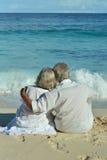 Couple sitting  on  tropical beach. Happy elderly couple sitting  on  tropical beach. Back view Royalty Free Stock Photo