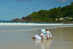 Couple sitting  on  tropical beach. Happy elderly couple sitting  on  tropical beach Royalty Free Stock Photo