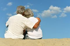 Happy elderly couple sitting. On tropical  beach Royalty Free Stock Image