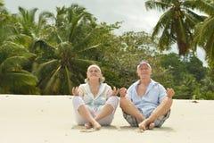 Happy elderly couple sitting. On tropical  beach Royalty Free Stock Photo