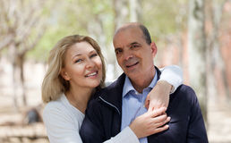 Happy elderly couple smiling in park and hug Stock Images
