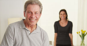 Happy Elderly couple standing in living room looking at camera Royalty Free Stock Images