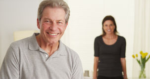 Happy Elderly couple standing in living room looking at camera Stock Images
