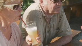 Happy elderly couple in sunglasses sitting in outdoors cafe with cocktails stock footage