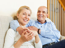 Happy elderly couple together on sofa in home Stock Images