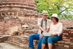 Elderly Asian tourist. Happy elderly couple Travel Ancient archaeological sites with history in Asia royalty free stock images