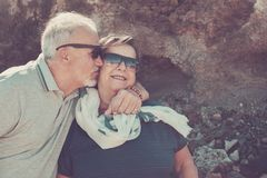 Couple of senior outdoor in vacation under the sunlight. Happy elderly couple on vacation in Tenerife with white hair and sunglasses smile and kiss each other on royalty free stock image