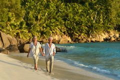 Couple walking on  tropical beach. Happy elderly couple walking on  tropical beach Royalty Free Stock Images