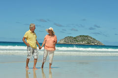 Couple walking on  beach. Happy elderly couple walking on  tropical beach Royalty Free Stock Photos
