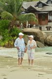 Elderly couple walking. Happy elderly couple walking on  tropical beach Royalty Free Stock Photography