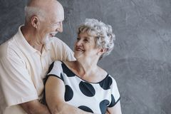 Happy elderly couple wedding anniversary. Happy elderly couple celebrating their wedding anniversary against concrete wall Royalty Free Stock Image