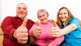 Happy elderly couple and young caregiver. Showing thumbs up Royalty Free Stock Photography