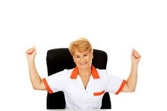 Happy elderly female doctor or nurse sitting behind the desk withd hands up Royalty Free Stock Photos