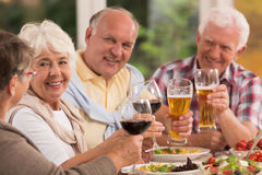 Happy elderly friends drinking beer royalty free stock photo