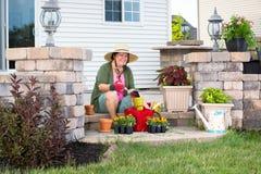 Happy elderly Grandma potting up plants Stock Photos
