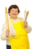 Happy elderly holding kitchen utensil Stock Photos