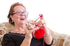 Happy elderly lady enjoying a joke. Laughing as she concentrates on her colorful festive red knitting while relaxing in a comfortable armchair, isolated on Stock Images