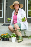 Happy elderly lady ready to transplant her flowers Royalty Free Stock Images